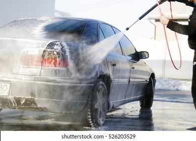 Man washes foam machine. Carwash. Washing machine at the station