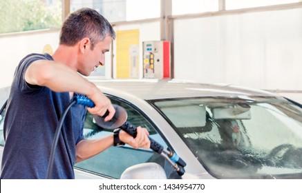man washes his car at the carwash using karcher