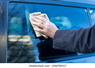 a man washes his car with a cloth . male hand holding a sponge wipes the glass of the car from dirt and dust . clean avtomobile