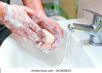 a man washes his hands with soap