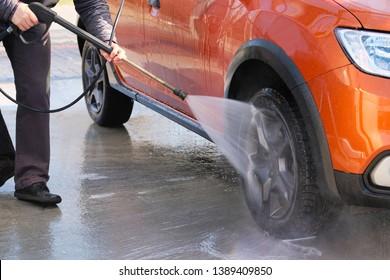 Man washes his orange car at car wash. Cleaning with water at self-service car wash. Soapy water runs down.