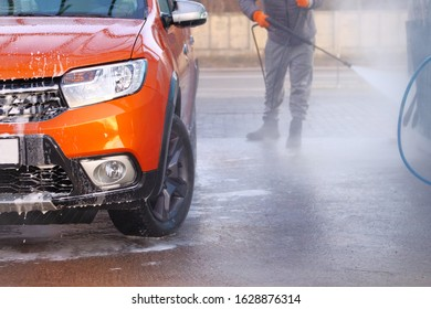 Man washes his orange car at car wash. Cleaning with a water jet at self-service car wash. Soapy water runs down.