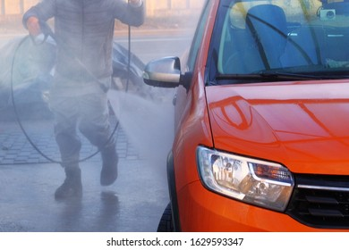 Man washes his orange car at car wash in outdoors. Cleaning with with a water jet at self-service car wash. Soapy water runs down.