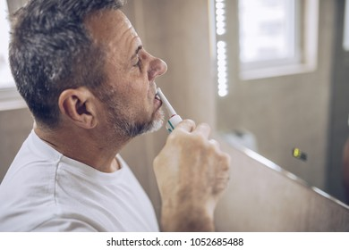 The man washes his teeth
