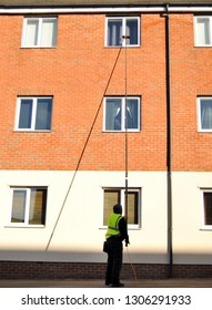 Man washing apartment windows with a very long pole