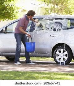 Man Washing Car In Drive