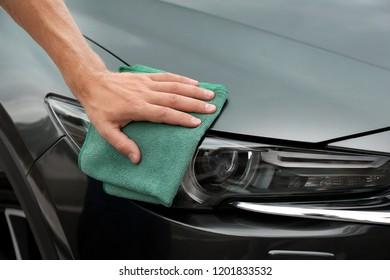 Man washing car headlight with rag, closeup