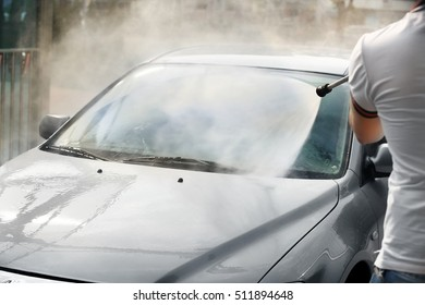 Man washing car with high pressure water