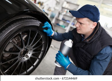 Man washing car tyres