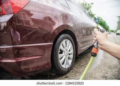 Man washing car using spray jet water - home people car clean concept