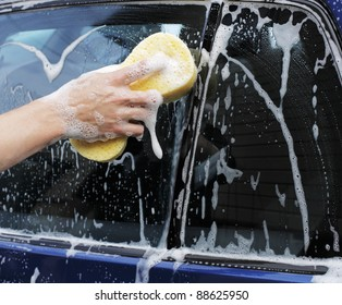 Man washing a car with a yellow sponge.