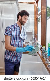 man washing dishes cleaning kitchen at home
