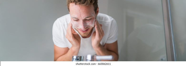 Man washing face banner panorama. Person cleansing with facial cleanser face wash soap in bathroom sink at home.