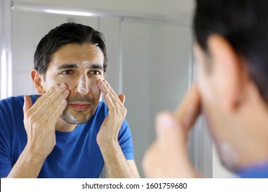 Man washing face with facial cleanser face wash soap looking at mirror in bathroom at home. Men skin care concept.