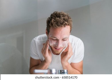 Man washing face with facial cleanser face wash soap in bathroom sink at home.