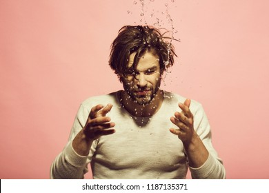 man washing face with water drops in morning. guy with long hair refreshing in underwear on pink background, hygiene and skincare, health and wakeup, everyday life, barbershop