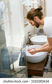 Man Washing Face. Young Male Cleaning Face In Bathroom. Portrait Of Handsome Man With Beard Washing Face Skin With Clean Water Over Bathroom Sink In Morning. Hygiene. High Quality Image.