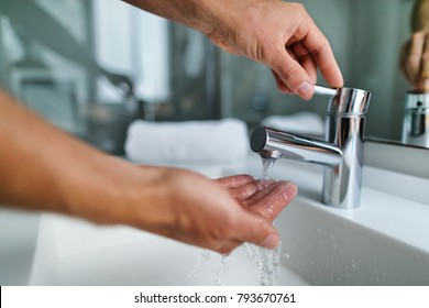 Man washing hands in bathroom sink at home checking temperature touching running water with hand. Closeup on fingers under hot water out of a faucet of a sink.