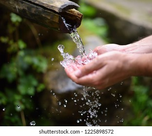 man washing hands in fresh, cold, potable water of mountain spring