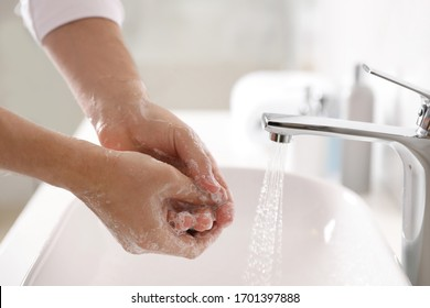 Man washing hands with soap over sink in bathroom, closeup