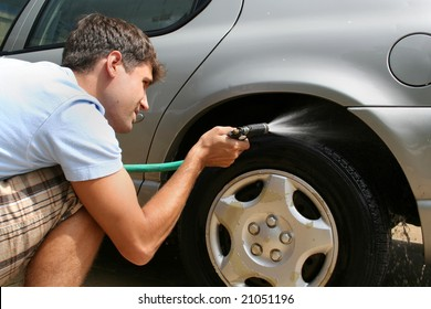 A man washing his car.  He is using a hose to wash the tires. Horizontally framed shot.