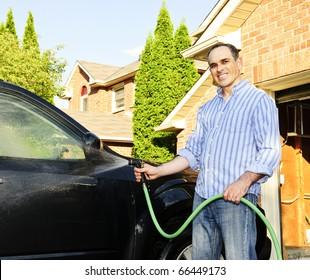Man washing his car on the driveway