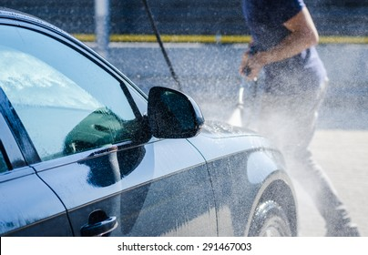 Man washing his car and pulverizing water all over with a dynamic look suggesting car wash services on a premium auto vehicle