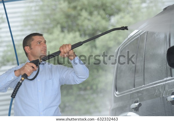 man washing his car with water hose