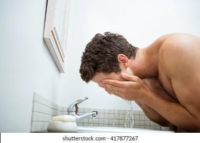 Man washing his face in the bathroom washbasin