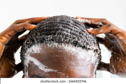 Man washing his hair with anti-dandruff shampoo, taking a shower with foam on his head holds fingers in hair in bathroom. African American for personal hygiene concept
