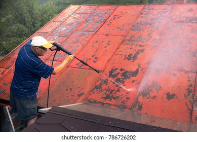 Man is washing the roof with a high pressure washer. Worker cleaning a red metal sheet roof by water.