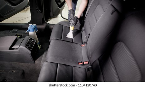man is washing seats of automobile, using washing vacuum cleaner in a service station, professional cleaning of interior of car