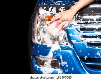 man washing a soapy blue car with a pink sponge.