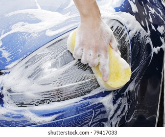 man washing a soapy blue car with a yellow sponge.