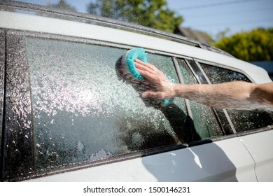 man washing a soapy white car with a colorful sponge.Manual car wash in car wash shop service with employee worker.car washing facility on sunny day