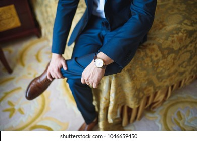 man with watch in suit sitting on bed at room