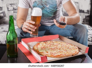 Man  watch TV and eating pizza with beer. Close up. Sitting on sofa