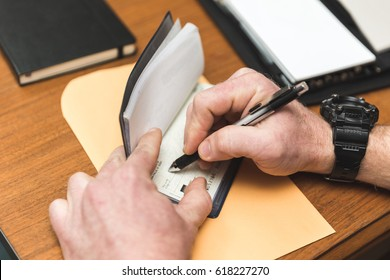 Man with watch writing a check in a checkbook. Envelope and notepads are nearby.