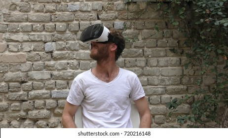 A man watches 360 degree video virtual reality using wearable head mounted display. The movie takes place in all directions and the beholder fills immersed in the scene