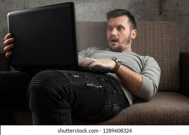 A man watches an adult video on a laptop while sitting on the couch. The concept of porn, masturbation, male needs, pervert, lust, desire, loneliness.
