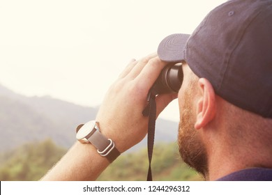 Man watches in the binoculars birds against the background of mountains. Observation of birds. Birdwatching
