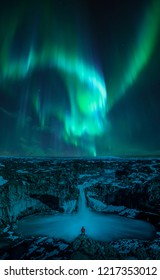 Man watches the Northern lights at Aldeyjarfoss, Iceland. Aurora borealis at famous waterfall in Iceland.