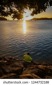 A man watches the Sunset over Orphelinat Bay, Noumea, New Caledonia
