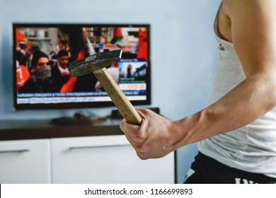 man watches TV news report about the protests. angry guy smashes TV with hammer. false news caused anger among viewers. explosive nature. An angry viewer is dissatisfied with the report of the channel