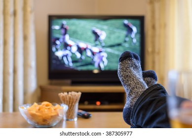 man watching American football match on TV (television) with feet on table, eating snacks - stock photo