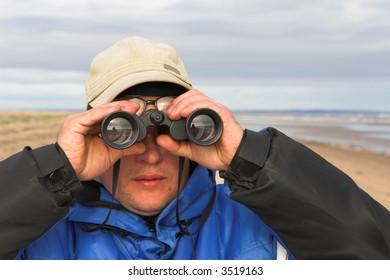 Man watching with binoculars to the horizon