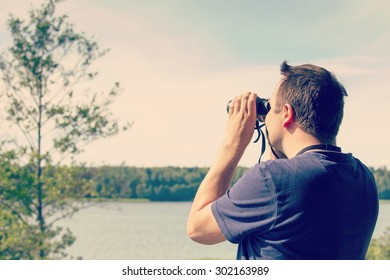 A man is watching birds and scenery with binoculars from high above the ground. The sea or lake is on the background. Image has a vintage effect applied.