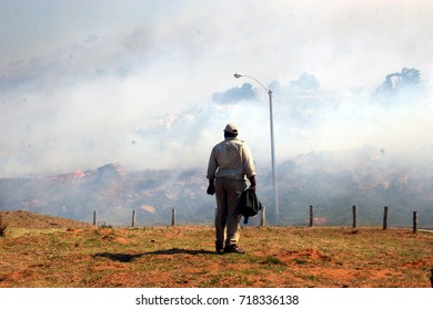 Man watching bush fire as it nears houses