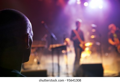Man is watching a concert of a Rock band