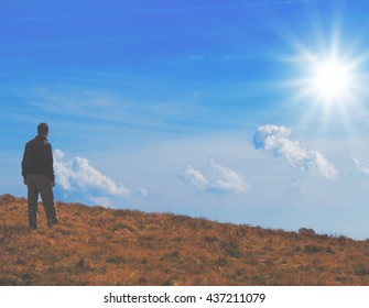 Man watching in the distance from a mountain top.